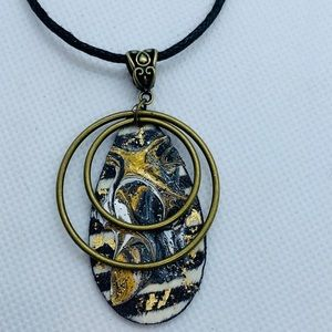 Jewelry - Gold and black wooden pendant.